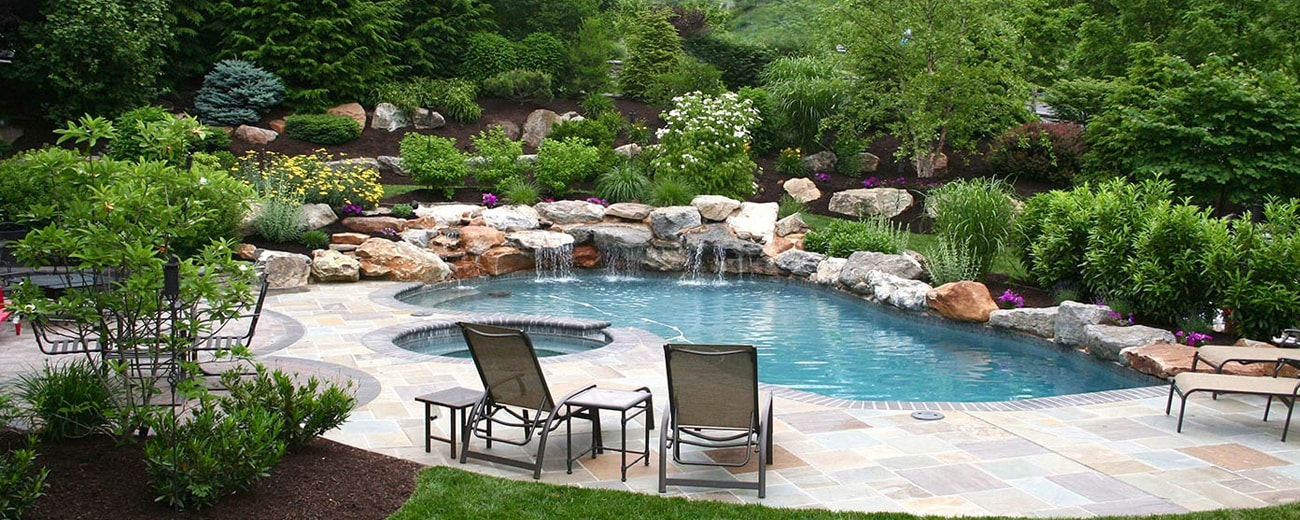custom poolscape with natural stone accents and waterfall